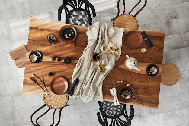 호두 나무 테이블, 복고풍 의자, 식기, 접시, 식탁보, 주전자, 음식, 장식 및 우아한 액세서리가있는 식당의 세련된 인테리어 디자인. 시멘트 바닥 .. 상위 뷰.