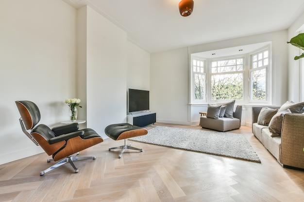 현대 아파트에 쿠션과 가죽 안락 의자가있는 편안한 소파가있는 대형 창문이있는 밝은 거실의 세련된 인테리어 디자인
