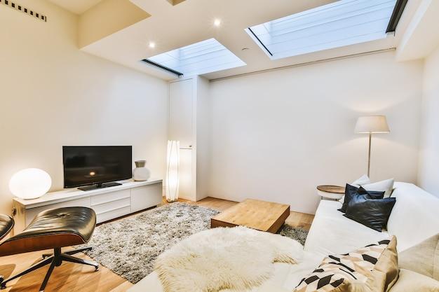 Стильный интерьер гостиной со светлой мебелью, мягким удобным диваном и ковром, с телевизором на шкафу в современной квартире с открытой кухней, белыми стенами и колонной.
