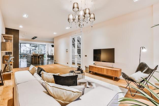 明るい家具と柔らかく快適なソファとカーペット、オープンキッチンと白い壁と柱のあるモダンなアパートメントのキャビネットにテレビを備えたリビングルームのスタイリッシュなインテリアデザイン。