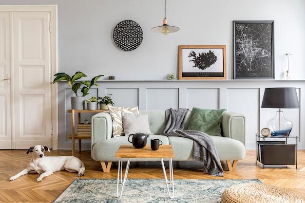 현대 민트 소파, 나무 콘솔, 커피 테이블, 램프, 식물, 포스터 프레임, 베개, 격자 무늬, 장식 및 바닥에 누워있는 아름다운 개가있는 거실의 세련된 인테리어 디자인.
