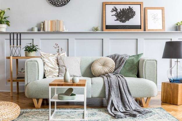 현대 민트 소파, 나무 콘솔, 큐브, 커피 테이블, 램프, 식물, 포스터 프레임, 베개, 격자 무늬, 장식 및 가정 장식의 우아한 액세서리가있는 거실의 세련된 인테리어 디자인.
