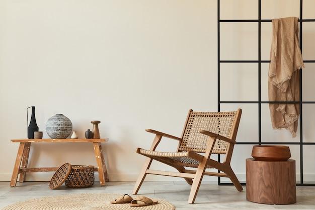 木製のアームチェア、コーヒーテーブル、ベンチ、籐の装飾、カーペット、エレガントなパーソナルアクセサリーを備えたリビングルームのスタイリッシュなインテリアデザイン。スペースの白い壁をコピーします。レンプレート。
