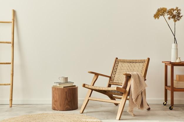 木製のアームチェア、コーヒーテーブル、家具、籐の装飾、ドライフラワー、エレガントなパーソナルアクセサリーを備えたリビングルームのスタイリッシュなインテリアデザイン。スペースの白い壁をコピーします。レンプレート。