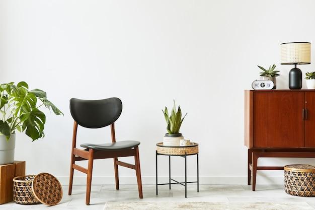 Стильный интерьер гостиной с деревянным ретро комодом, стулом, несколькими растениями, корзиной из ротанга, декором, лампой, часами и элегантными личными аксессуарами. скопируйте космическую белую стену. шаблон.