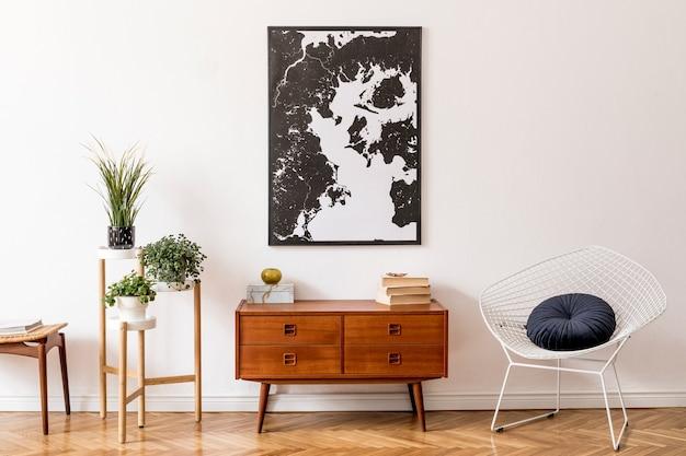 나무 복고풍 옷장, 흰색 안락 의자, 발판 및 우아한 개인 액세서리가있는 거실의 세련된 인테리어 디자인. 벽에 프레임. 빈티지 홈 장식.