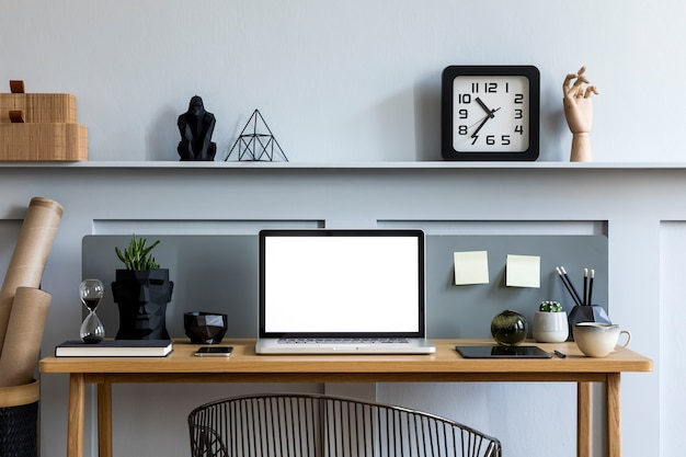 Stylish interior of home office room with laptop screen, wooden desk, plant, books, notes, chair, wood paneling and elegant office accessories in design apartment.