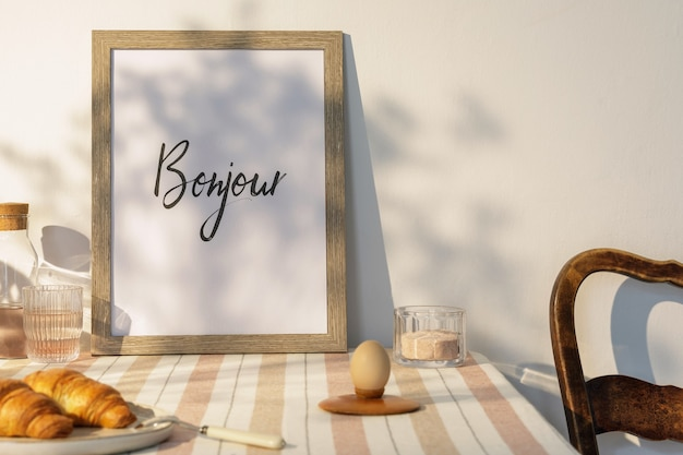 Stylish interior of kitchen space with wooden table, brown mock up photo frame, beige tablecloth, food and kitchen accessories. country side mood. summer vibe.