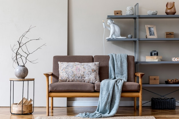 Stylish interior of living room at cozy apartment with brown wooden sofa, coffe table, gray bookstand , pillow, plaid and elegant accessories. beige and japandi concept. modern home staging. .