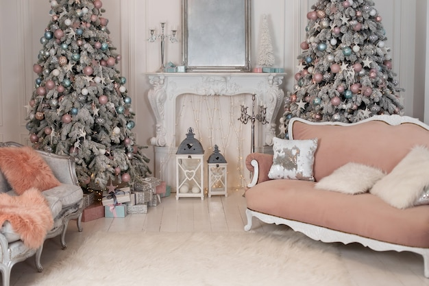 Stylish interior of living room with christmas tree and glowing garlands fireplace and pink sofa