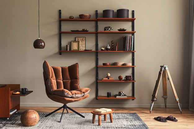 Stylish interior of living room with design brown armchair, wooden bookcase, pendant lamp, carpet decor, picture frames and elegant personal accessories in modern retro home decor..