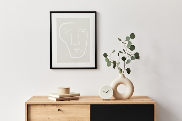 Stylish interior of living room with frame, wooden commode, book, leaf in ceramic vase and elegant personal accessories. minimalist concept of home decor.