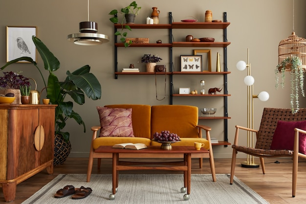 Stylish interior of living room with honey yellow sofa, wooden bookcase, plants, commode, picture frame, carpet, decoration