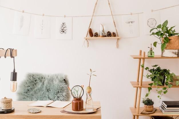 木製の机、森のアクセサリー、アボカドの植物、竹の棚、植物、籐の装飾が施されたホームオフィススペースのスタイリッシュなインテリア。ニュートラルな家の装飾。