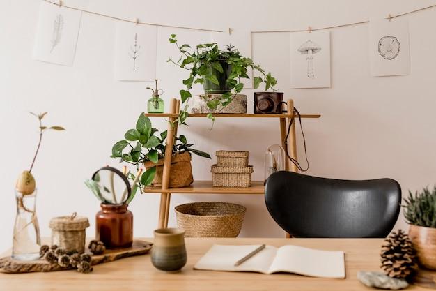 나무 책상, 숲 액세서리, 아보카도 식물, 대나무 선반, 식물 및 등나무 장식으로 홈 오피스 공간의 세련된 인테리어. 중립적 인 가정 장식.