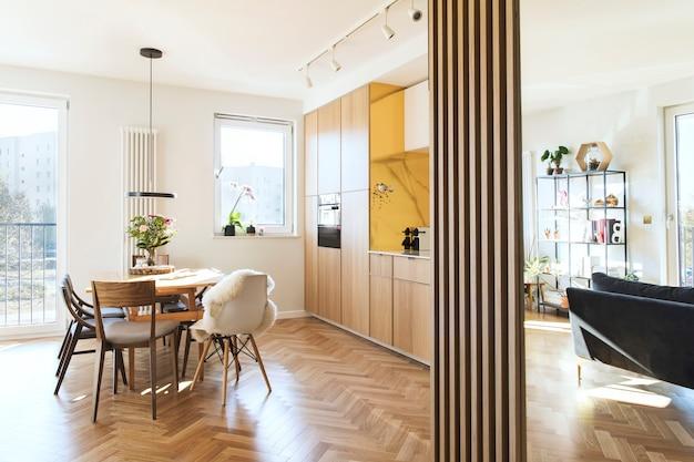 Стильный интерьер кухни и столовой с дизайнерским семейным столом и кухонными принадлежностями