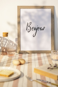 木製のテーブル、茶色のモックアップフォトフレーム、ベージュのテーブルクロス、食品、キッチンアクセサリーを備えたキッチンスペースのスタイリッシュなインテリア。田舎の気分。夏の雰囲気。