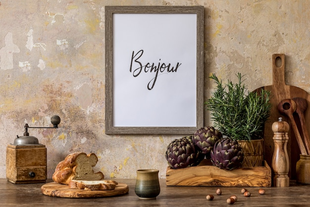 Стильный интерьер кухонного пространства с деревянным столом, коричневой рамкой для фото, хлебом, чашкой чая, зеленью, овощами и кухонными принадлежностями в концепции домашнего декора ваби-саби.