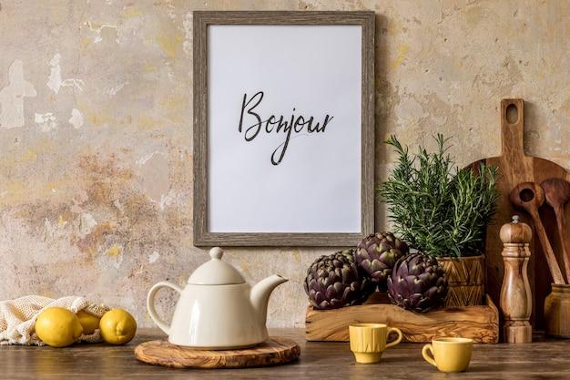 Стильный интерьер кухонного пространства с деревянным столом, коричневой фоторамкой, зеленью, овощами, чайником, чашкой и кухонными принадлежностями в концепции домашнего декора ваби саби.