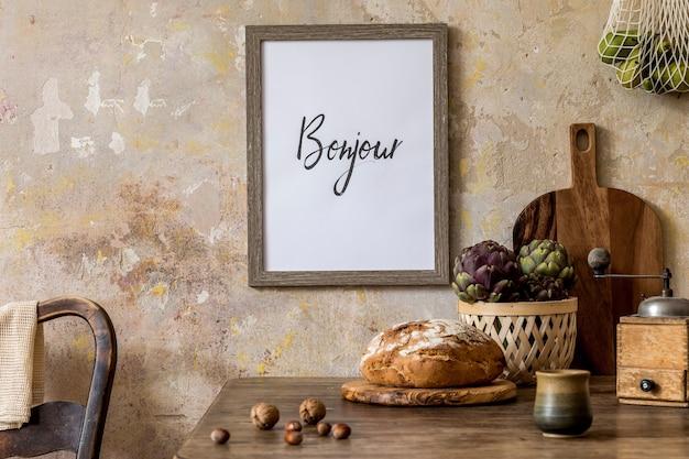 Стильный интерьер кухонного пространства с деревянным столом, коричневой фоторамкой, зеленью, овощами, чайником, чашками и кухонными принадлежностями.