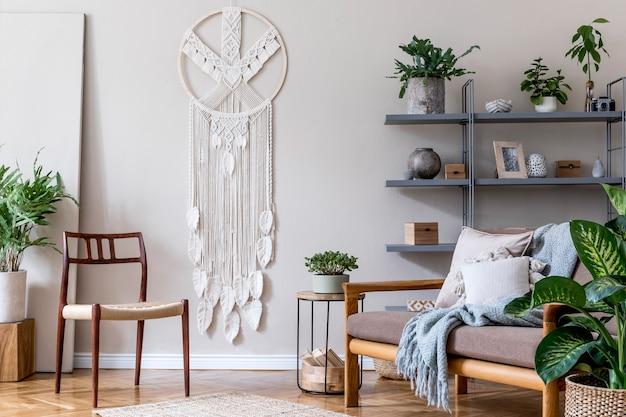 茶色のソファ、コーヒーテーブル、本立て、たくさんの植物、マクラメ、エレガントなアクセサリーを備えた居心地の良いアパートのリビングルームのスタイリッシュなインテリア。ベージュとjapandiのコンセプト。現代のホームステージング。テンプレート。