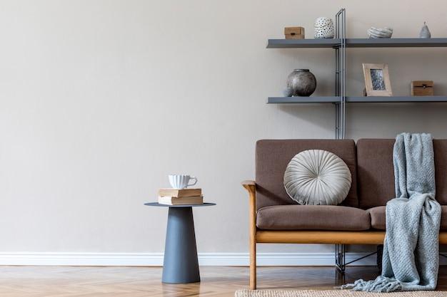 Стильный интерьер гостиной в уютной квартире с коричневым деревянным диваном, журнальным столиком, серой книжной стойкой, подушкой, пледом и элегантными аксессуарами. концепция бежевого и японского. современная домашняя постановка. .