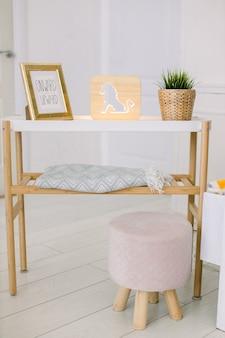 거실의 세련된 인테리어. 가정 장식. 사진 프레임이있는 커피 테이블, 사자 그림이있는 장식용 나무 램프, 고리 버들 화분의 인공 식물 및 분홍색 의자 푸프.