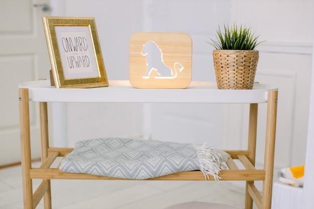 거실의 세련된 인테리어. 가정 장식. 사진 프레임, 사자 그림 장식 나무 램프, 고리 버들 화분에 인공 식물이있는 커피 테이블.