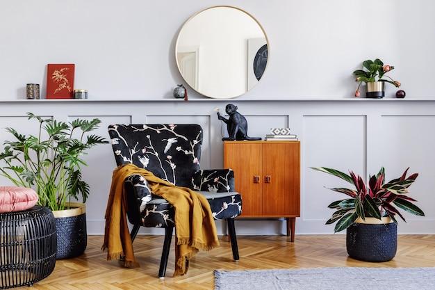 Стильный интерьер гостиной с дизайнерским креслом, деревянным винтажным комодом, круглым зеркалом, полкой, растениями, журнальным столиком, декором, серой стеной и персональными аксессуарами в домашнем декоре.