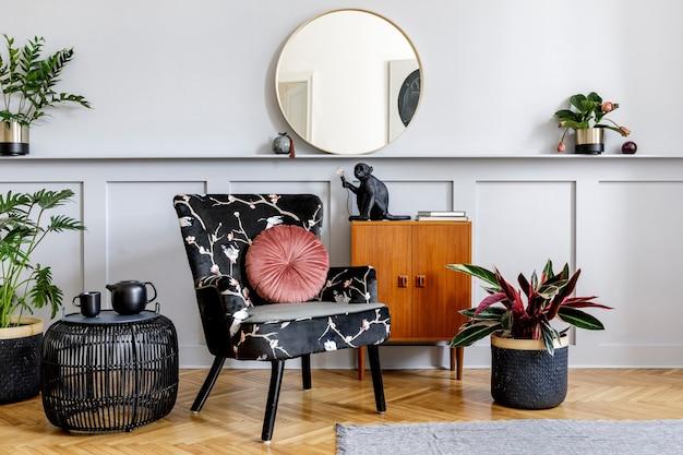 Стильный интерьер гостиной с дизайнерским креслом, деревянным винтажным комодом, круглым зеркалом, полкой, растениями, журнальным столиком из ротанга, чайником, лампой, серой стеной и персональными аксессуарами в домашнем декоре.