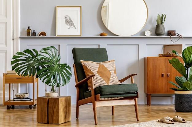 デザインアームチェア、木製のヴィンテージの便器、丸い鏡、棚、熱帯の葉、コーヒーテーブル、装飾、カーペット、家の装飾のパーソナールアクセサリーを備えたリビングルームのスタイリッシュなインテリア。