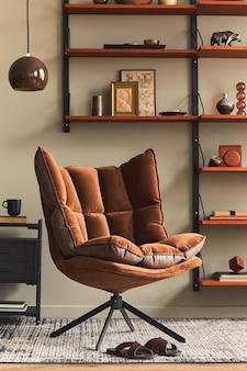 현대적인 복고풍 가정 장식의 디자인 갈색 안락 의자, 나무 책장, 펜던트 램프, 카펫 장식, 액자 및 우아한 개인 액세서리가있는 거실의 세련된 인테리어.