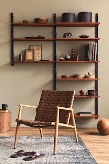 デザインの茶色のアームチェア、木製の本棚、ペンダント ランプ、カーペットの装飾、額縁、モダンなレトロな家の装飾のエレガントなパーソナル アクセサリーとリビング ルームのスタイリッシュなインテリア.