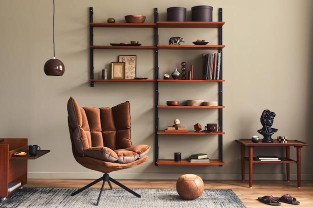 デザインブラウンのアームチェア、木製の本棚、ペンダントランプ、カーペットの装飾、額縁、モダンなレトロな家の装飾のエレガントなパーソナルアクセサリーを備えたリビングルームのスタイリッシュなインテリア。