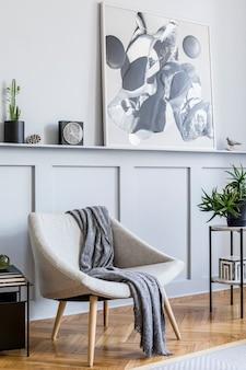 Стильный интерьер гостиной с дизайнерским серым креслом, подушками, журнальным столиком, картинами, растениями, декором, черными часами и элегантными личными аксессуарами в современном домашнем декоре.