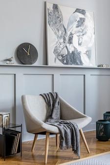 デザイングレーのアームチェア、枕、コーヒーテーブル、絵画、植物、装飾、黒い時計、モダンな家の装飾のエレガントなパーソナルアクセサリーを備えたリビングルームのスタイリッシュなインテリア。