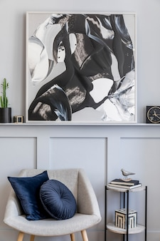 회색 안락 의자, 베개, 대리석 의자, 그림, 선인장, 장식, 검은 색 시계 및 현대 가정 장식의 우아한 개인 액세서리가있는 거실의 세련된 인테리어.