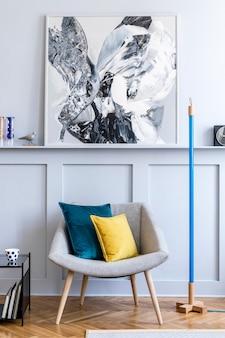 디자인 회색 안락 의자, 베개, 그림, 가구, 네온, 장식, 검은 색 시계 및 현대 가정 장식의 우아한 개인 액세서리가있는 거실의 세련된 인테리어.