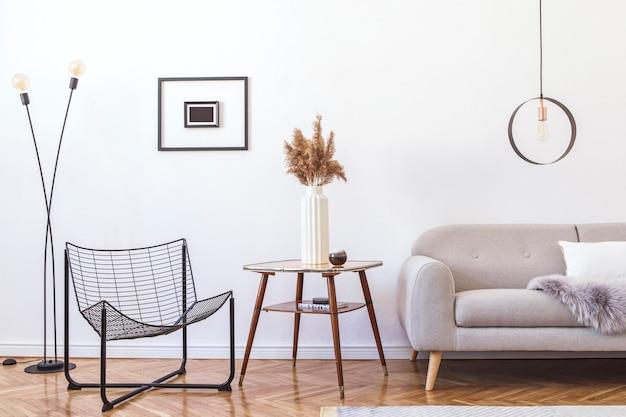 Стильный интерьер гостиной с дизайнерским серым диваном, мебелью, круглым подвесным светильником, элегантными аксессуарами и фоторамкой в минималистичном домашнем декоре.