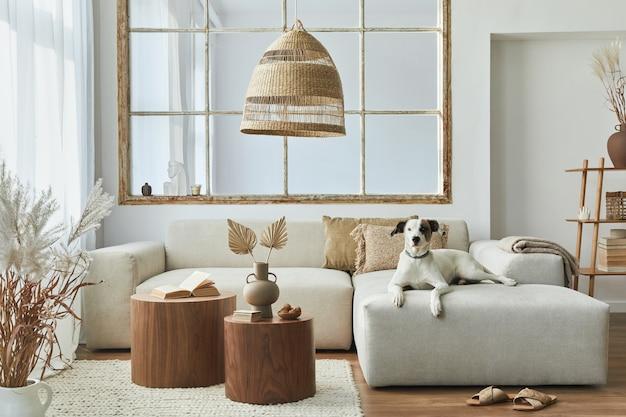 デザインモジュラーソファ、家具、コーヒーテーブル、籐の装飾、ドライフラワー、モダンな家の装飾のエレガントなアクセサリーを備えたリビングルームのスタイリッシュなインテリア。