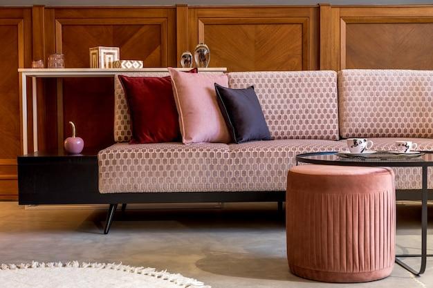 ピンクのベルベットのソファ、エレガントなプーフ、コーヒー テーブル、枕、装飾、エレガントなパーソナル アクセサリーを備えた、リビング ルームのスタイリッシュなインテリア。モダンな家の装飾とホームステージング..
