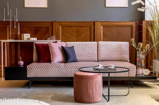 ピンクのベルベットのソファ、エレガントなプーフ、コーヒー テーブル、植物、枕、装飾、エレガントなパーソナル アクセサリーを備えた、リビング ルームのスタイリッシュなインテリア。モダンな家の装飾とホームステージング..