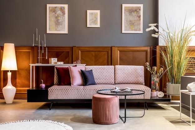 デザインピンクのベルベットのソファ、エレガントなプーフ、コーヒーテーブル、植物、枕、装飾、エレガントなパーソナルアクセサリーを備えたリビングルームのスタイリッシュなインテリア。モダンな家の装飾とホームステージング。