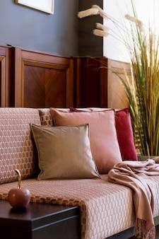 ピンクのベルベットのソファ、ベロアの枕、格子縞、装飾、エレガントなパーソナル アクセサリーを備えた、リビング ルームのスタイリッシュなインテリア。モダンな家の装飾とホームステージング..