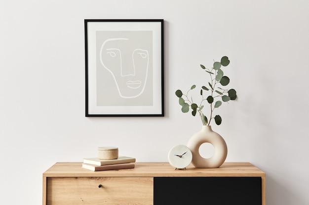 フレーム、木製の箪笥、本、陶製の花瓶の葉、エレガントなパーソナルアクセサリーを備えたリビングルームのスタイリッシュなインテリア。家の装飾のミニマリストの概念。