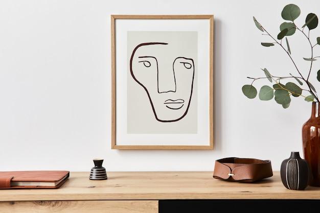 모의 포스터 프레임, 나무 옷장, 책, 세라믹 꽃병의 유칼립투스 잎 및 우아한 개인 액세서리가있는 거실의 세련된 인테리어. 가정 장식의 미니멀리스트 개념. 주형.
