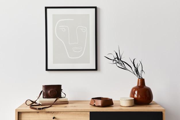 포스터 프레임, 나무 옷장, 책, 세라믹 꽃병의 잎, 사진 카메라 및 우아한 개인 액세서리가있는 거실의 세련된 인테리어. 가정 장식의 미니멀리스트 개념. 주형.