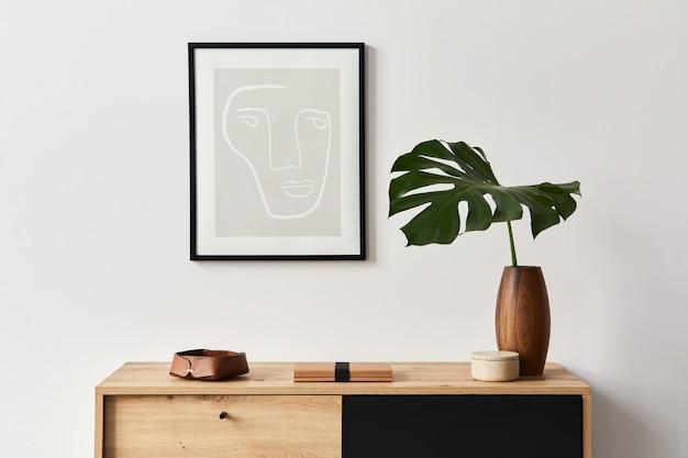 포스터 프레임, 나무 옷장, 책, 세라믹 꽃병의 열대 잎 및 우아한 개인 액세서리가있는 거실의 세련된 인테리어. 가정 장식의 미니멀리스트 개념. 주형.