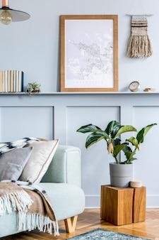 Стильный интерьер гостиной с рамкой для плаката, дизайнерским диваном, деревянным кубом, подвесным светильником, растением, ковром, подушками, пледом, книгами, часами и элегантными личными аксессуарами в современном домашнем декоре.