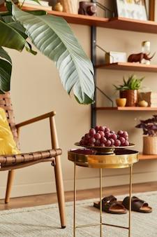 籐のアームチェア、木製の本棚、植物、プーフ、額縁、カーペット、装飾、家の装飾のエレガントなアクセサリーを備えたリビングルームのスタイリッシュなインテリア。テンプレート。
